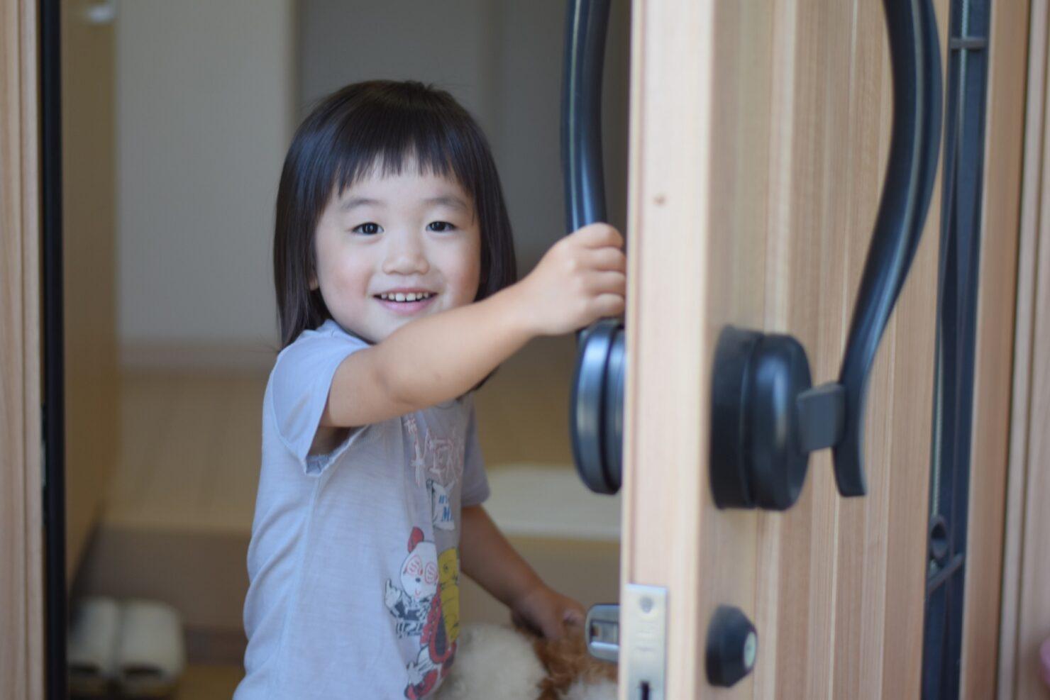 玄関ドアを開ける子供